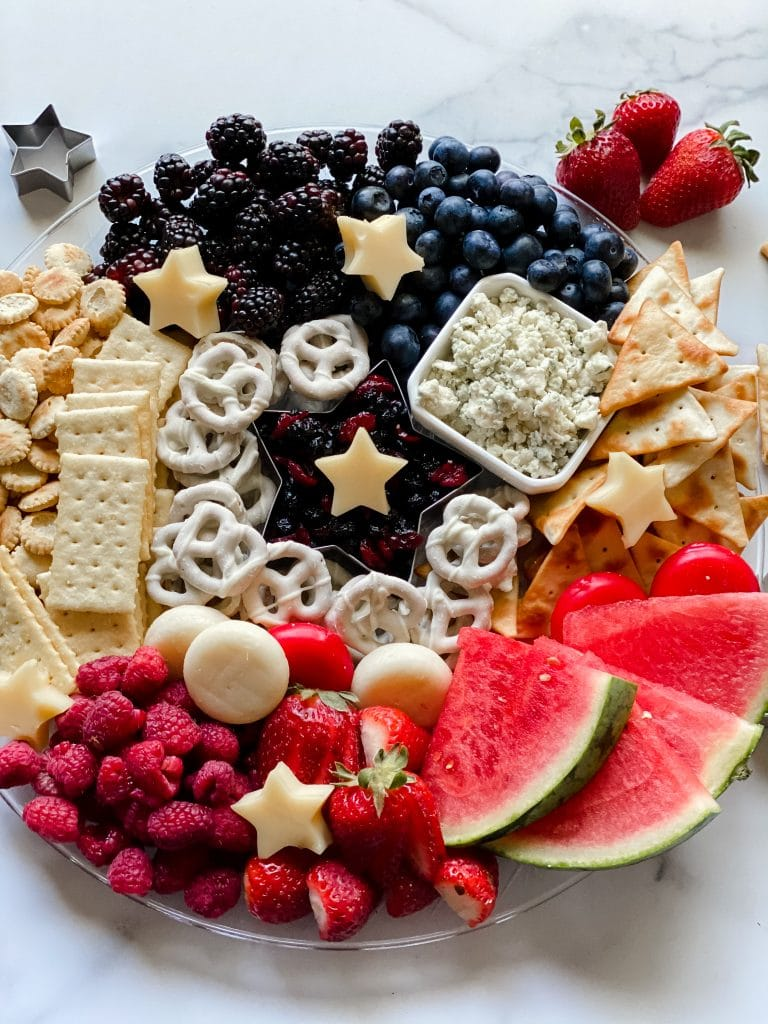 beautiful patriotic charcuterie board with crackers, cheese, and fruit on a tray with a granite surface underneath.