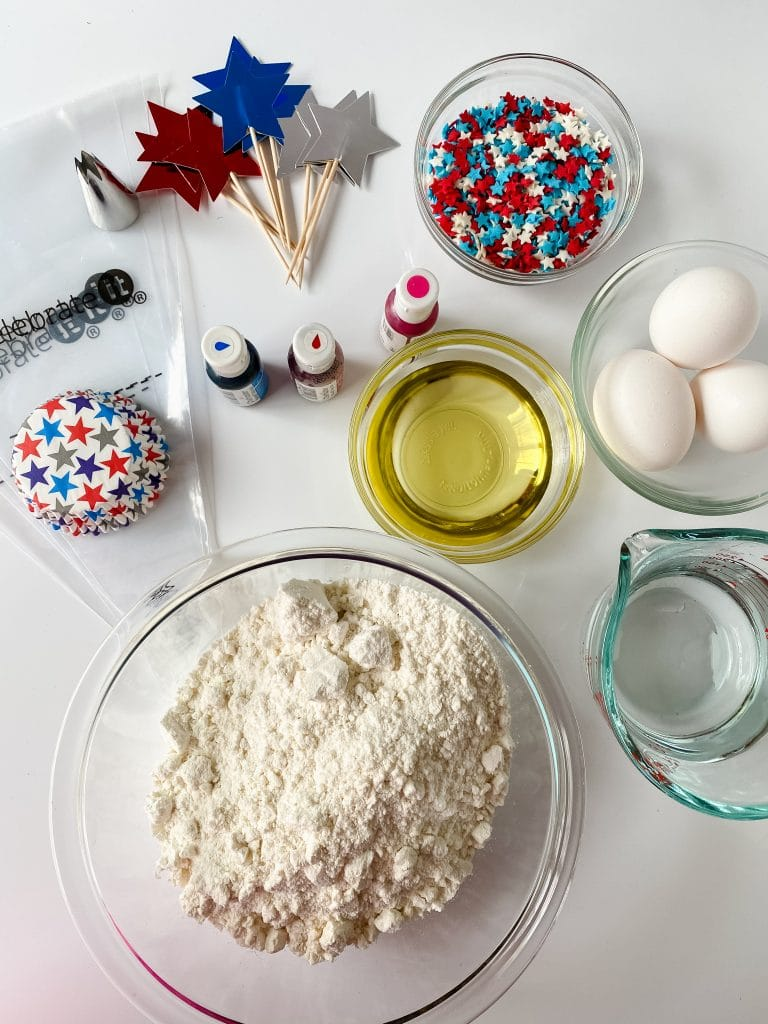 Ingredients for patriotic cupcakes including red, white, and blue cupcake toppers.