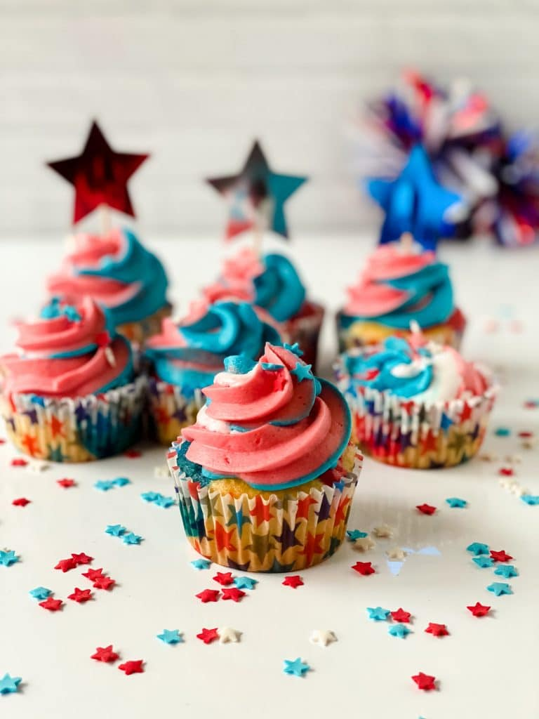 Gorgeous Fourth of July Cupcakes on a table with star-shaped sprinkles.