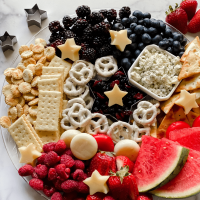 A tray filled with cheeses, fruits, pretzels, and crackers.