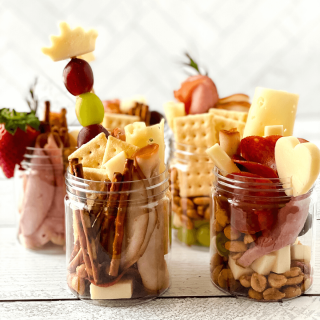 Jars filled with sliced meats, cheeses, crackers, fruit, nuts and pretzels.