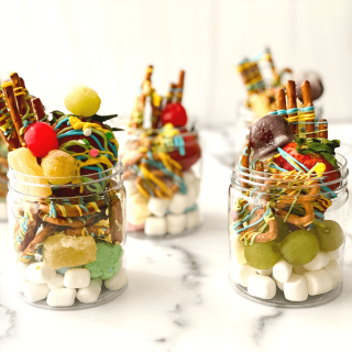 Jars filled with marshmallows, candied grapes, dried fruit, and candied pretzels.