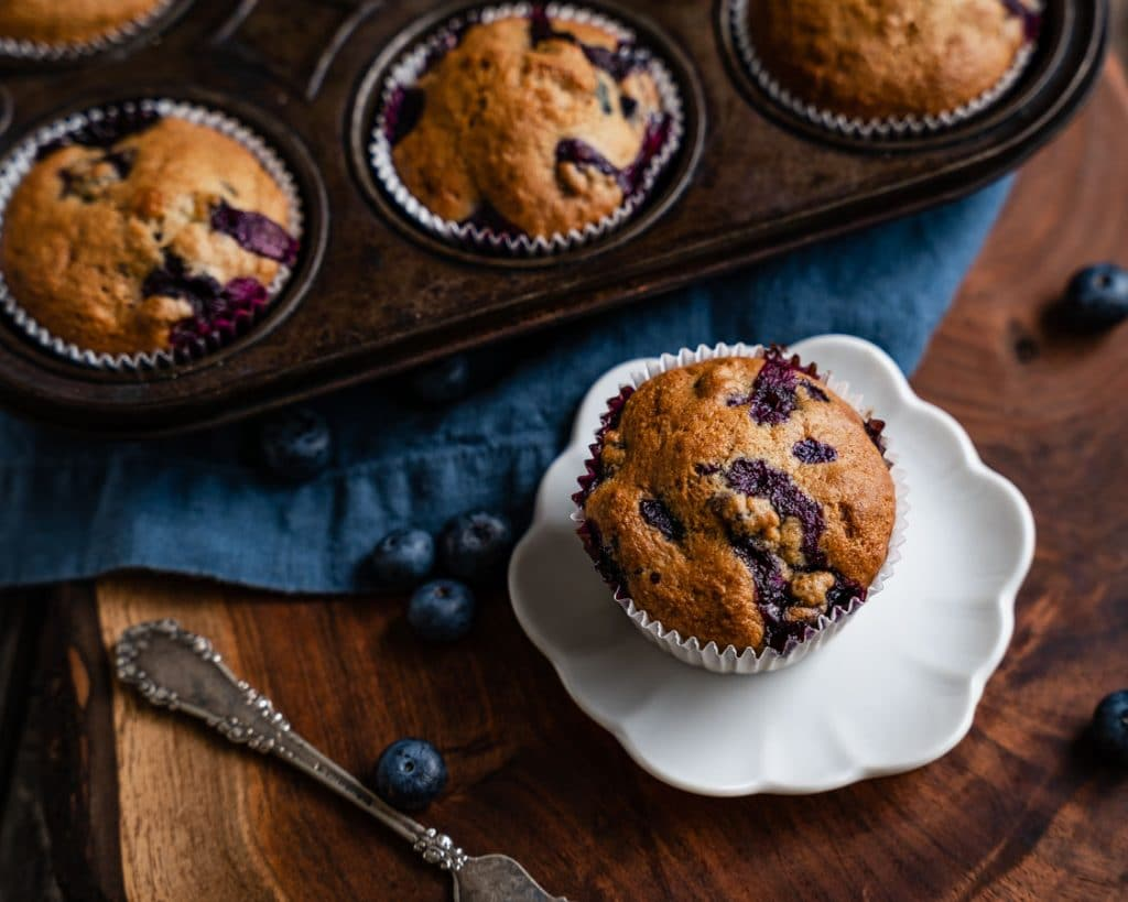 Top view of a blueberry banana muffin sitting on a small plate with the muffin pan filled with muffins behind it.