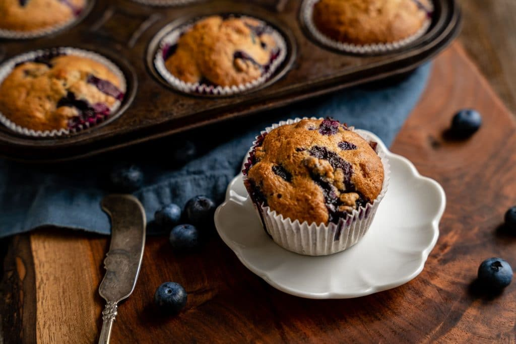 3/4 view of a blueberry banana muffin sitting on a white plate with the filled muffin tin behind it.