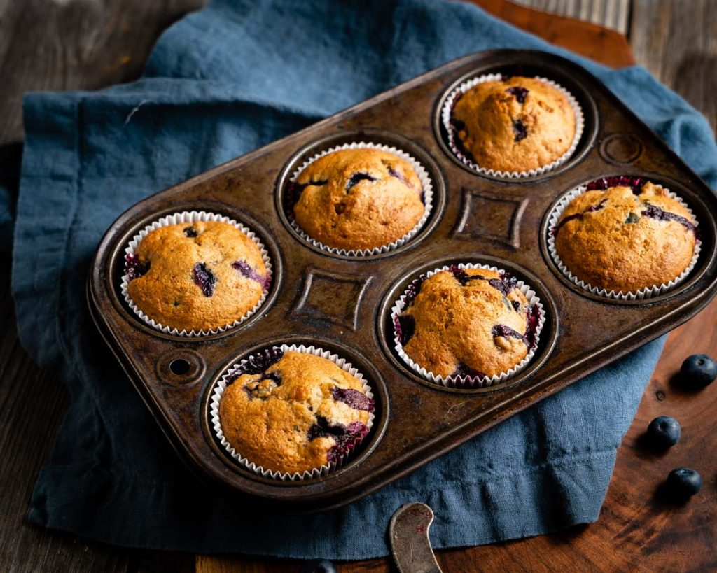 Top down view of a muffin tin filled with baked blueberry muffins