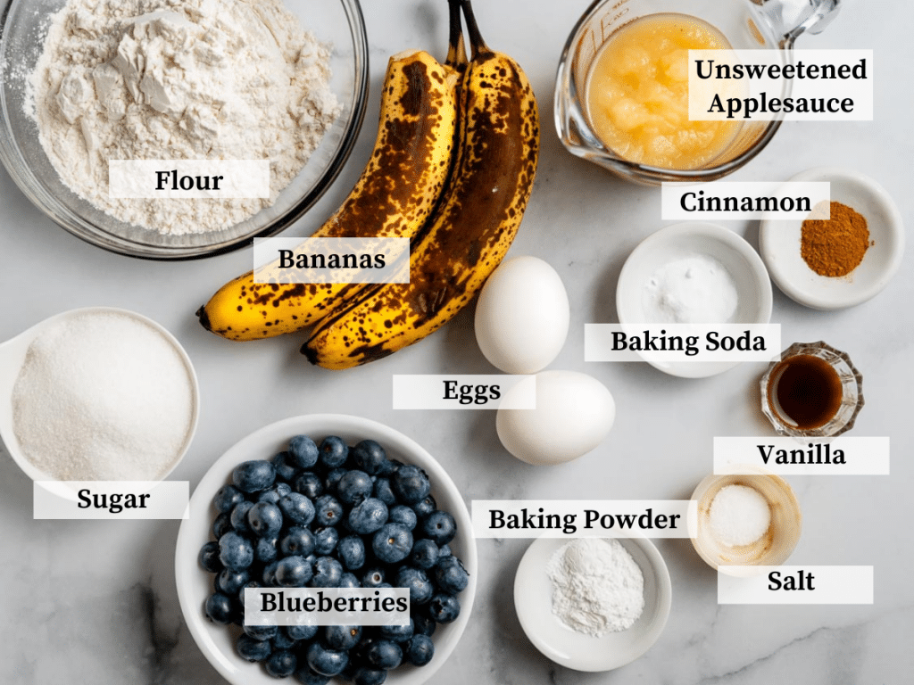 Top down view of the ingredients in banana blueberry muffins including flour, sugar, blueberries, bananas, eggs, cinnamon, vanilla, salt, baking powder and soda, cinnamon and applesauce