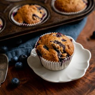 Close up side view of a berry muffin sitting on a white plate