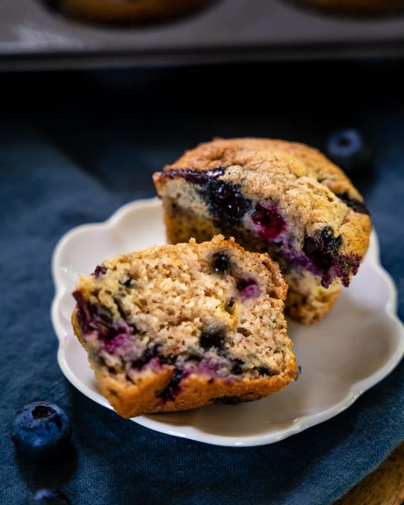 A muffin cut in half showing baked berries.