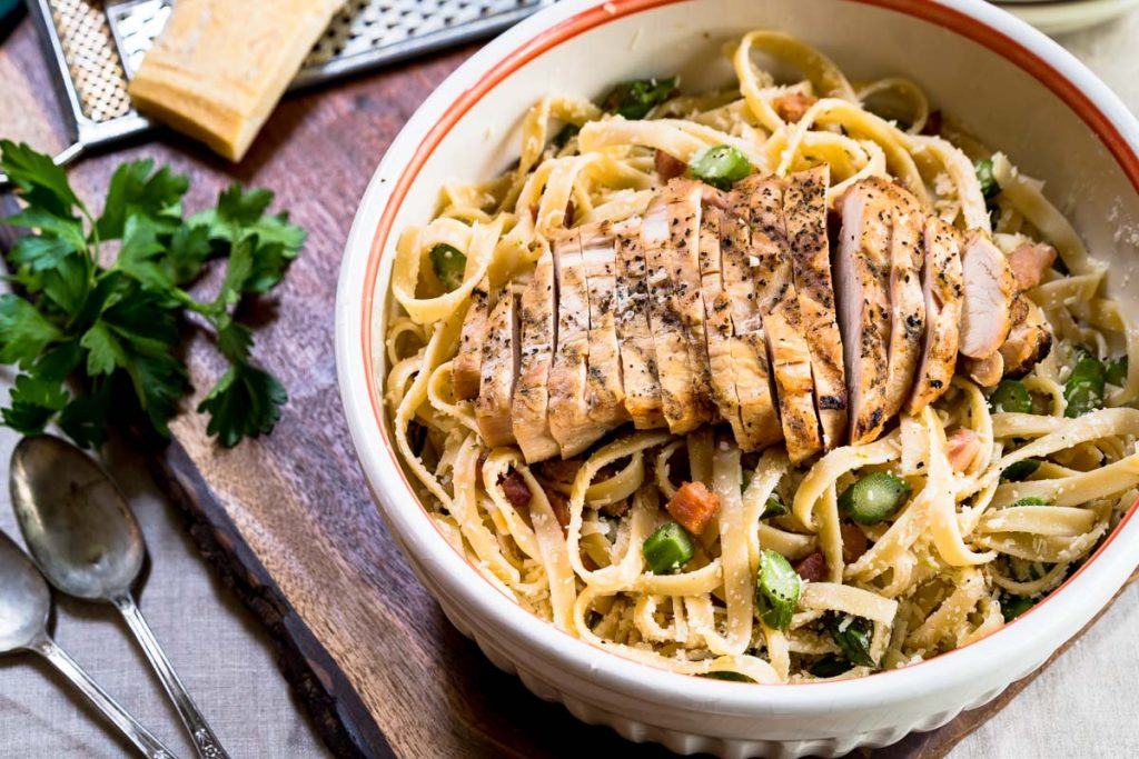 Top down photo of a bowl of fettuccine pasta topped with grilled chicken, asparagus and grated cheese.