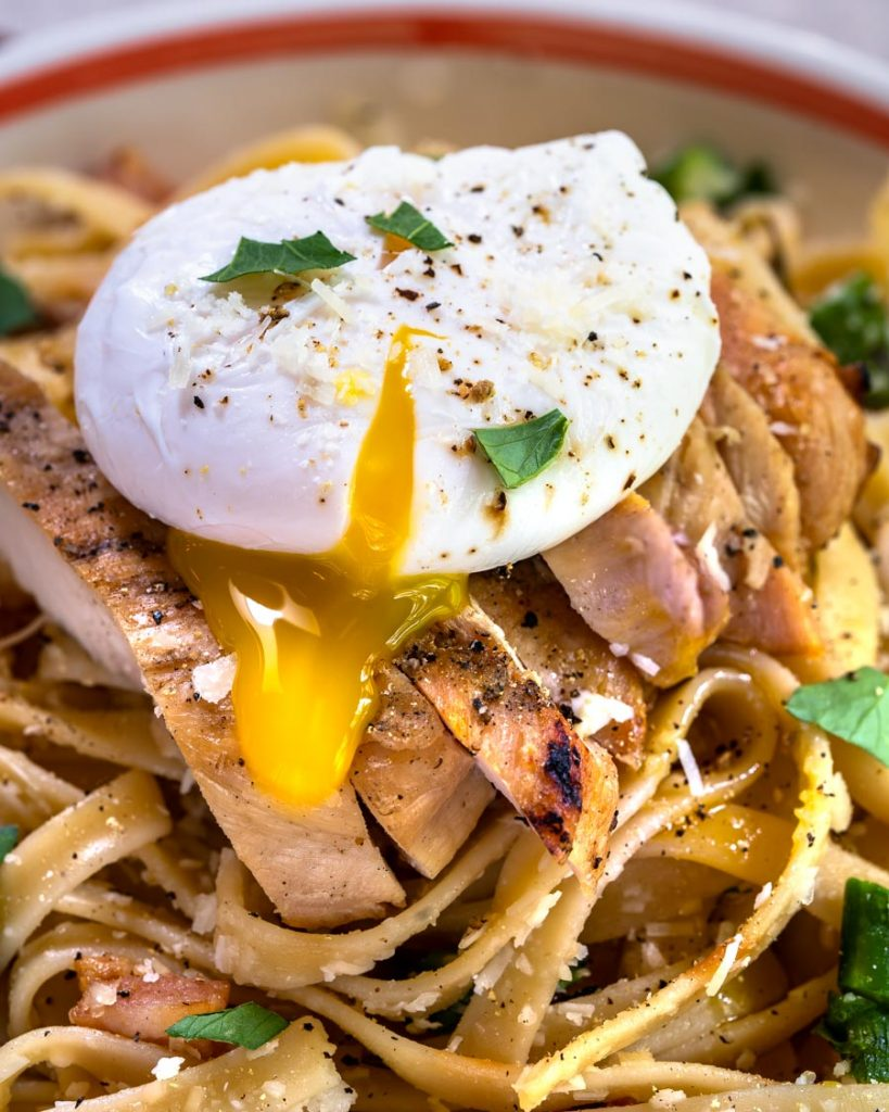 Close up of the yolk of a poached egg running over fettuccine pasta and grilled chicken.