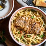 Top down photo of a bowl of fettuccine pasta topped with grilled chicken.