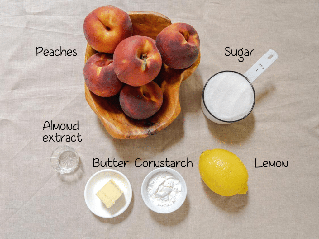 Ingredients used to make peach pie including peaches, almond extract, butter, cornstarch, lemon, and sugar.