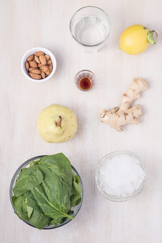 Ingredients for pear smoothie: almonds, ginger, pear, spinach, lemon juice, water, crushed ice, vanilla.
