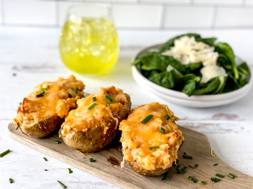Three twice-baked potatoes in an image with a drink and salad,