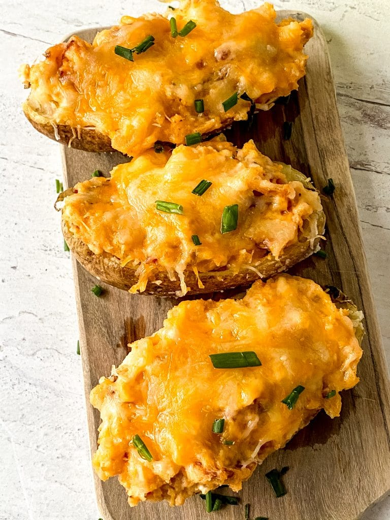 Three twice-baked potatoes on a board close-up.