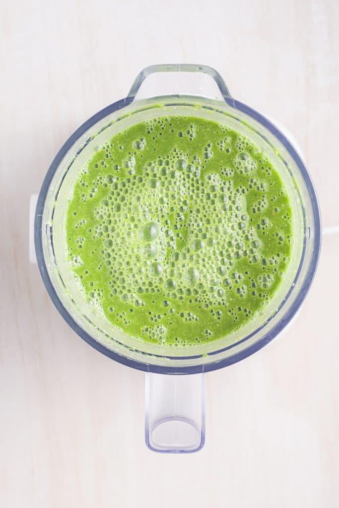 Green smoothie in a blender bowl.