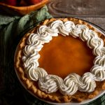 3/4 view of a no-bake peach pie with swirled whipped cream around the edges.