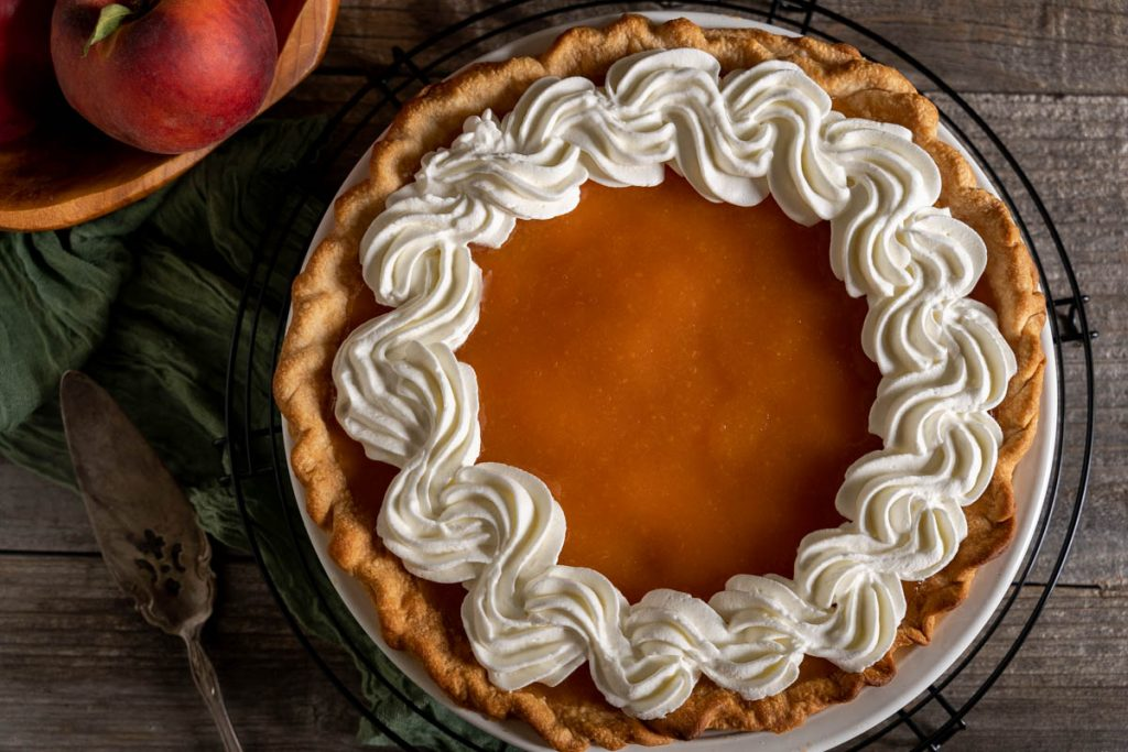 Top down view of a glazed fresh peach pie decorated with a piped whip cream.