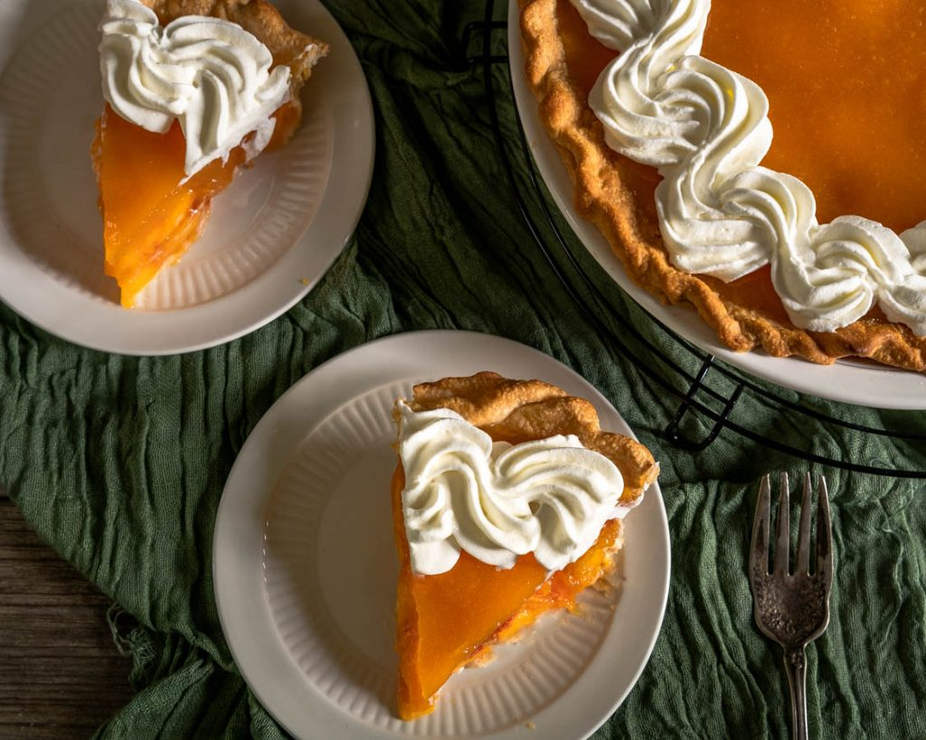 Top down view of two slices of peach pie garnished with whipped cream with a partial view of the whole pie in the background.