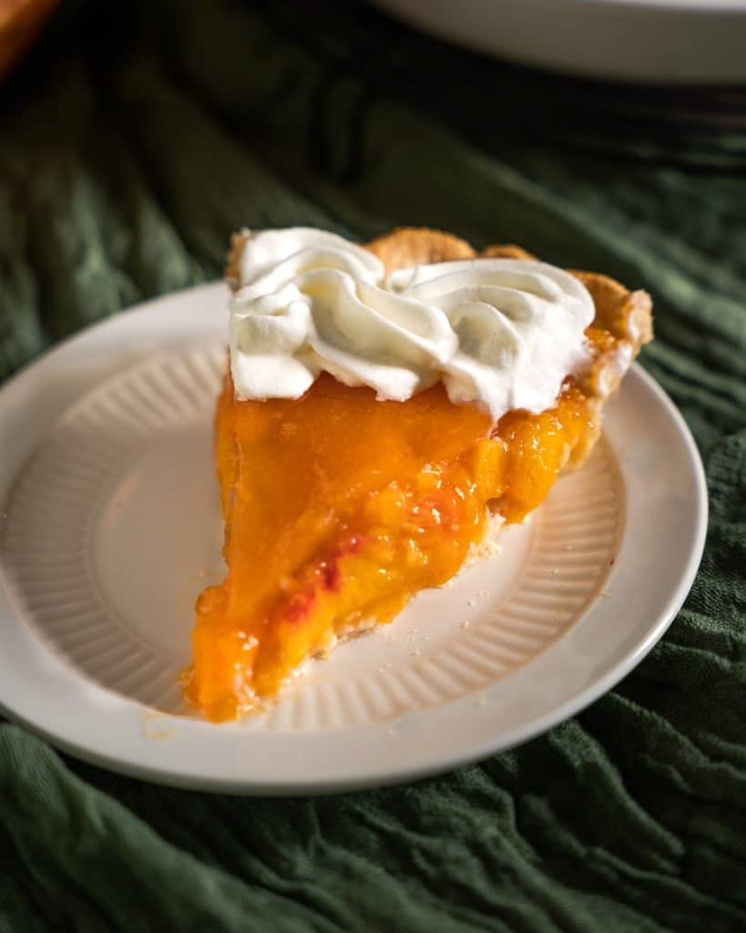 Table view of a slice of fresh peach pie with a whip cream garnish.