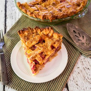 Top down view of a slice of rhubarb custard pie with a lattice top sitting on a plate with the whole pie in the background.