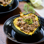 3/4 angle view of one half of a baked acorn squash stuffed with sausage and fennel.