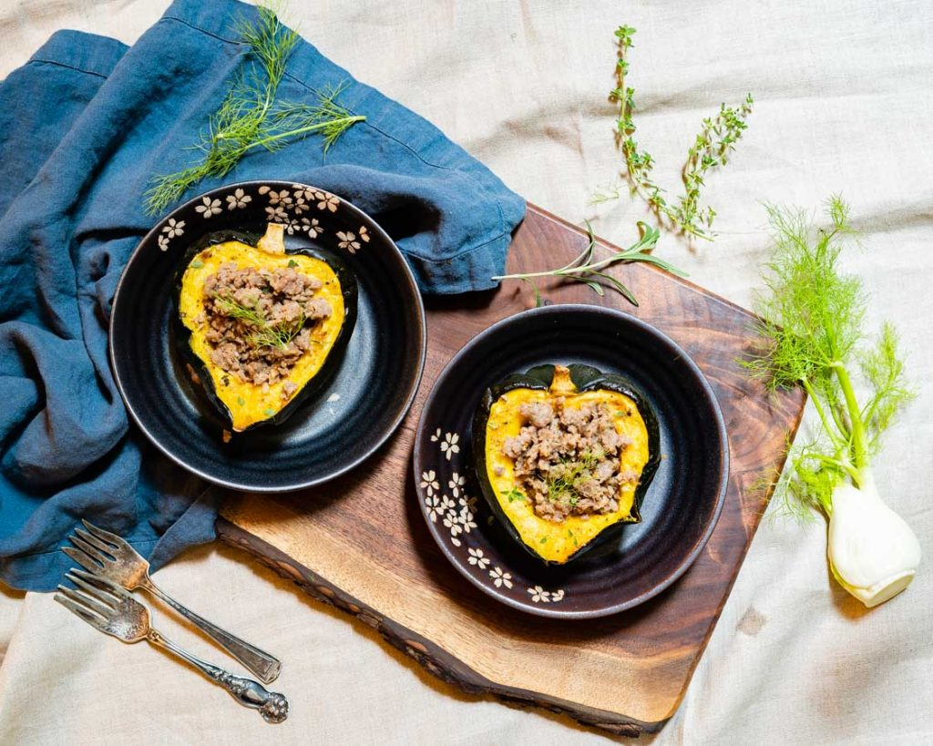 Two sausage-stuffed acorn squash halves, on a wooden board with herbs around.