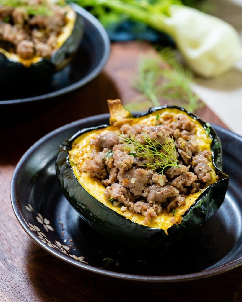 Close-up of sausage-stuffed acorn squash with fennel frond on top.