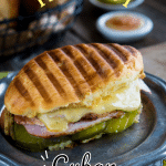 Grilled Cuban Sandwich filled with dill pickle slices, ham, roasted pork, and Swiss cheese on a grey metal plate.