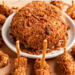 Top down photo of a round bacon covered cheeseball surrounded by football shaped mini cheeseballs
