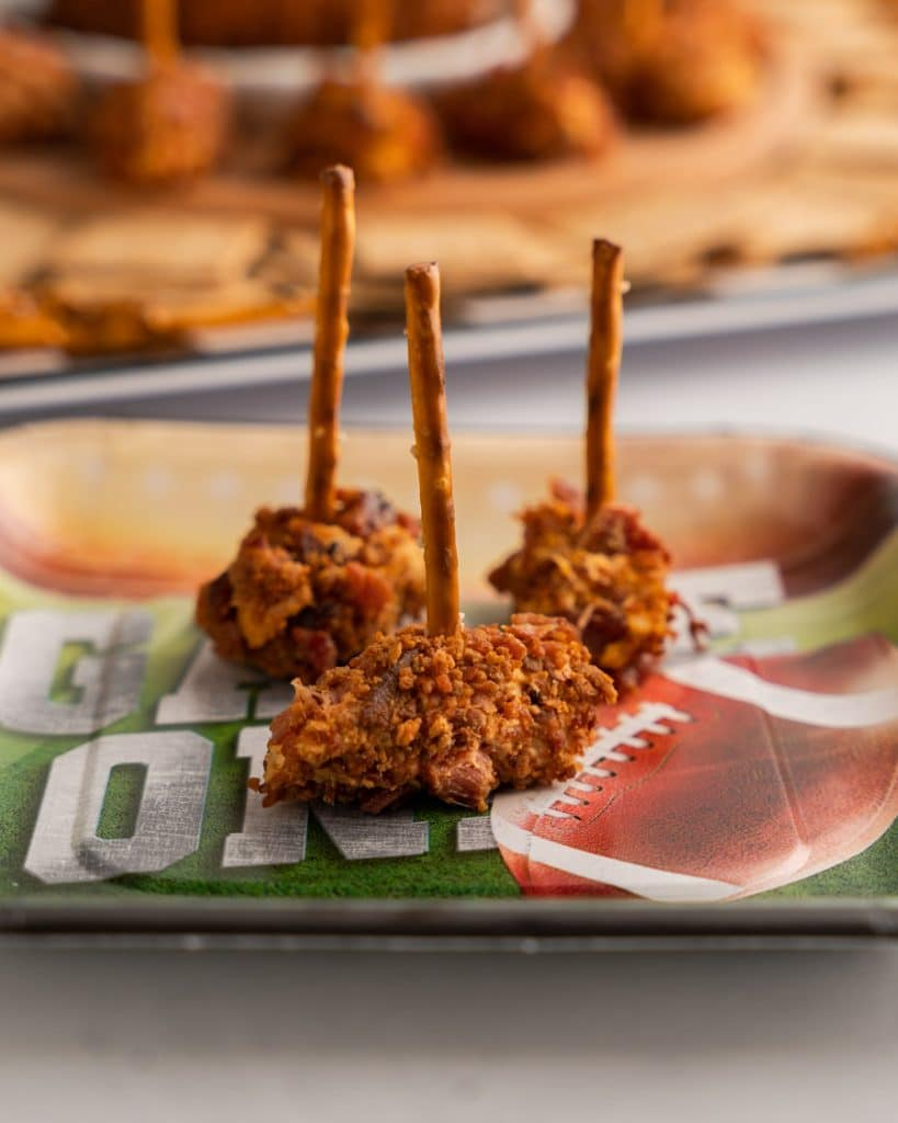 Close up table photo of three football shaped cheeseballs rolled in bacon bits and speared with pretzel sticks.
