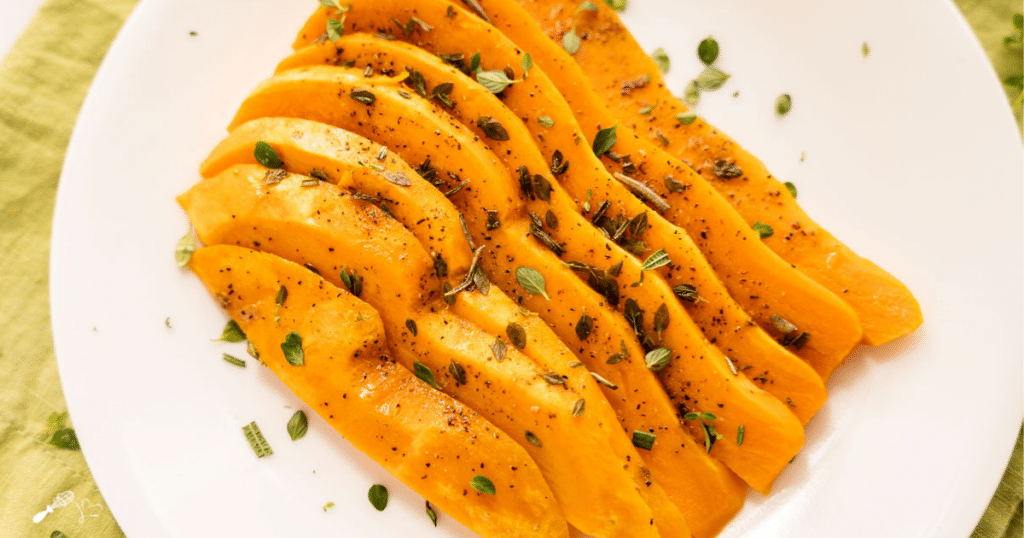 Top down photo of sliced sweet potatoes garnished with fresh herbs.