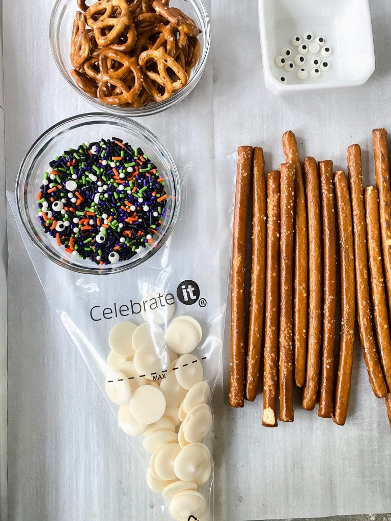 Ingredients for chocolate covered pretzels, including candy melts, sprinkles, and pretzels.