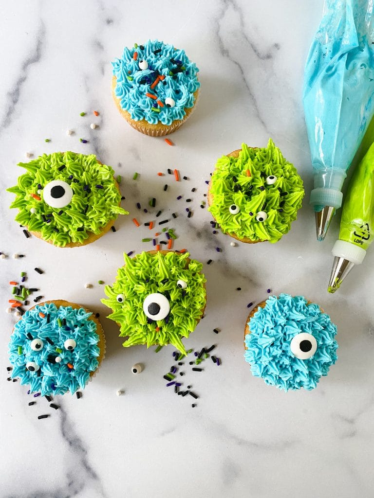 Monster cupcakes close-up with green and blue frosting and candy eyes.