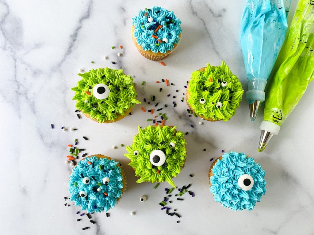monster decorated cupcakes shown with piping bags filled with frosting.