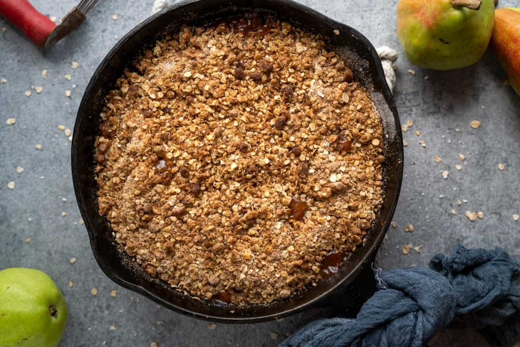 Top Down photo of a cast Iron skillet filled with baked pear crisp topped with streusel with oats.