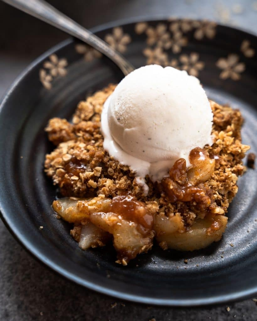 Individual serving of pear crisp shown in a dish with ice cream.