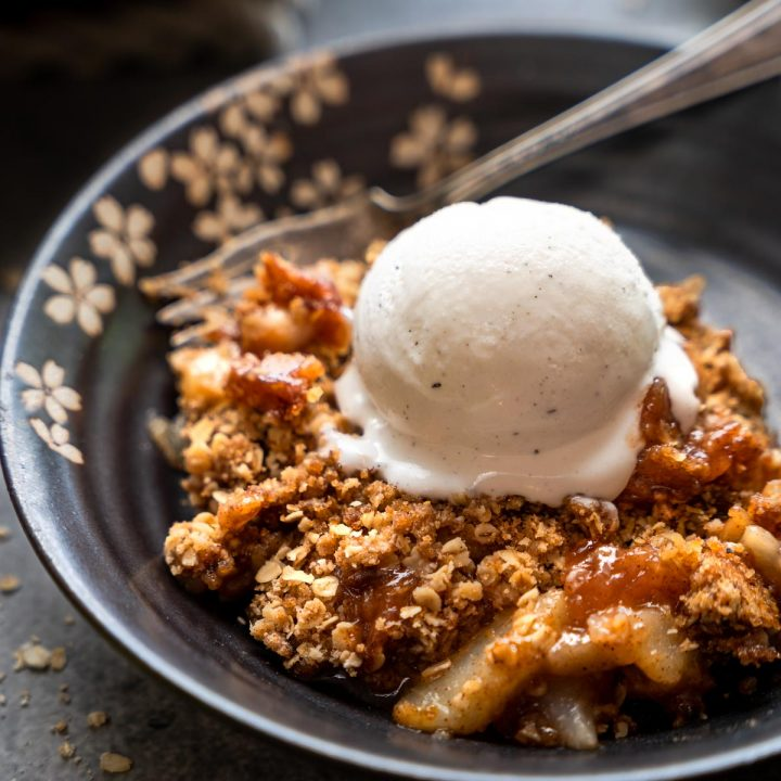 3/4 view of a serving of pear crisp topped with ice cream.