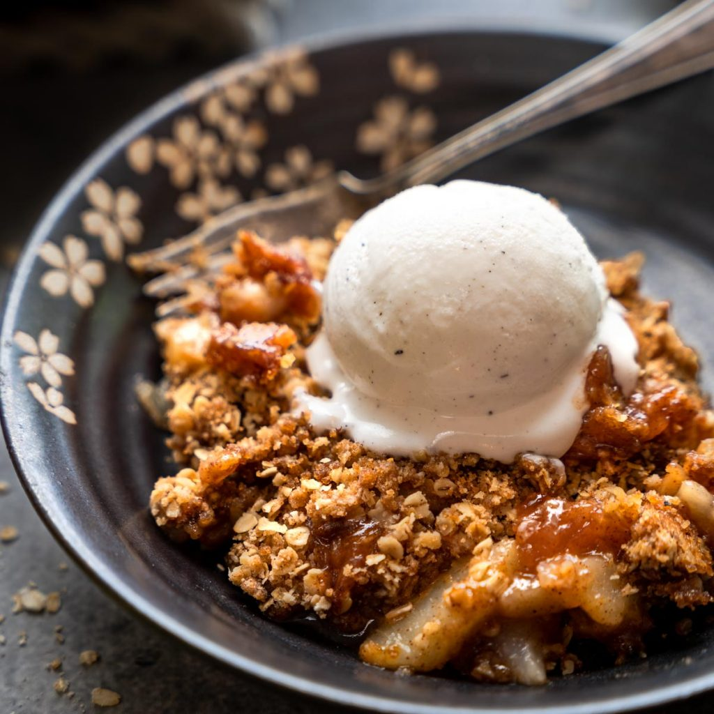 3/4 view of a dish of pear crisp topped with vanilla ice cream.