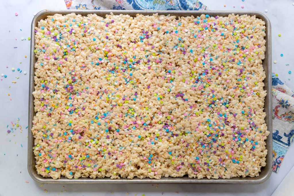 Top down image of a pan of Rice Krispie Treats garnished with colorful sprinkles.