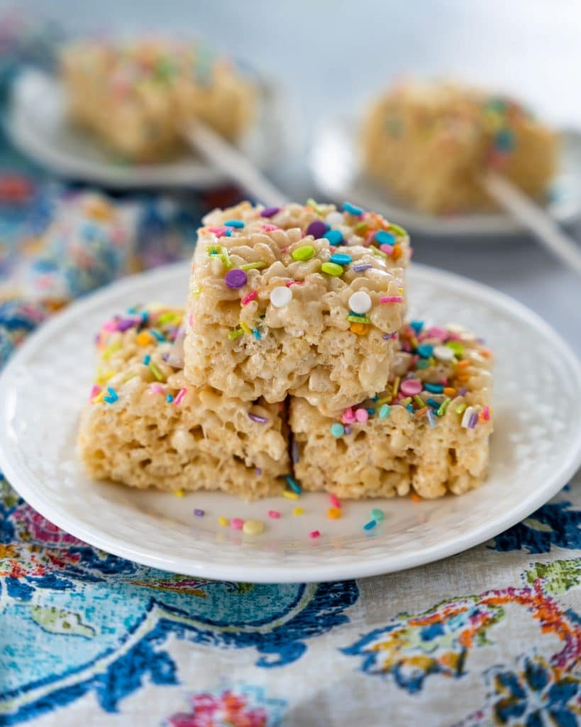 Table view of 3 Rice Krispie Cookies garnished with colorful sprinkles stacked on a plate.