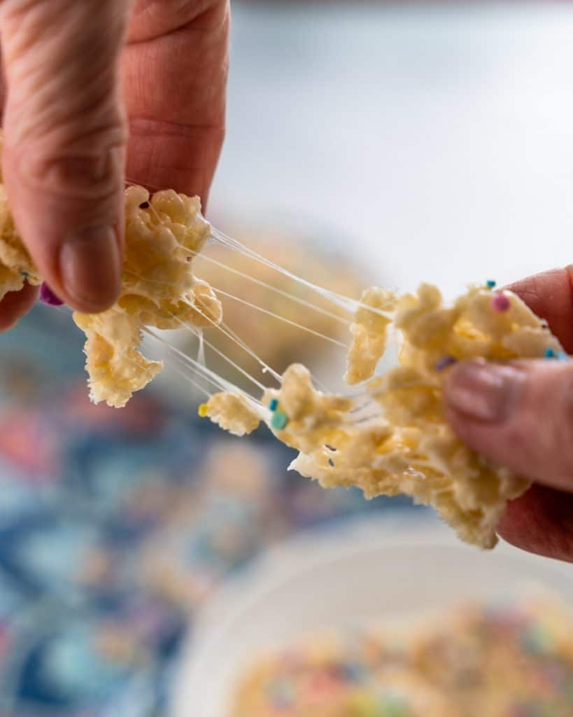 A rice krispie treat being pulled apart showing the stretch of melted marshmallow .