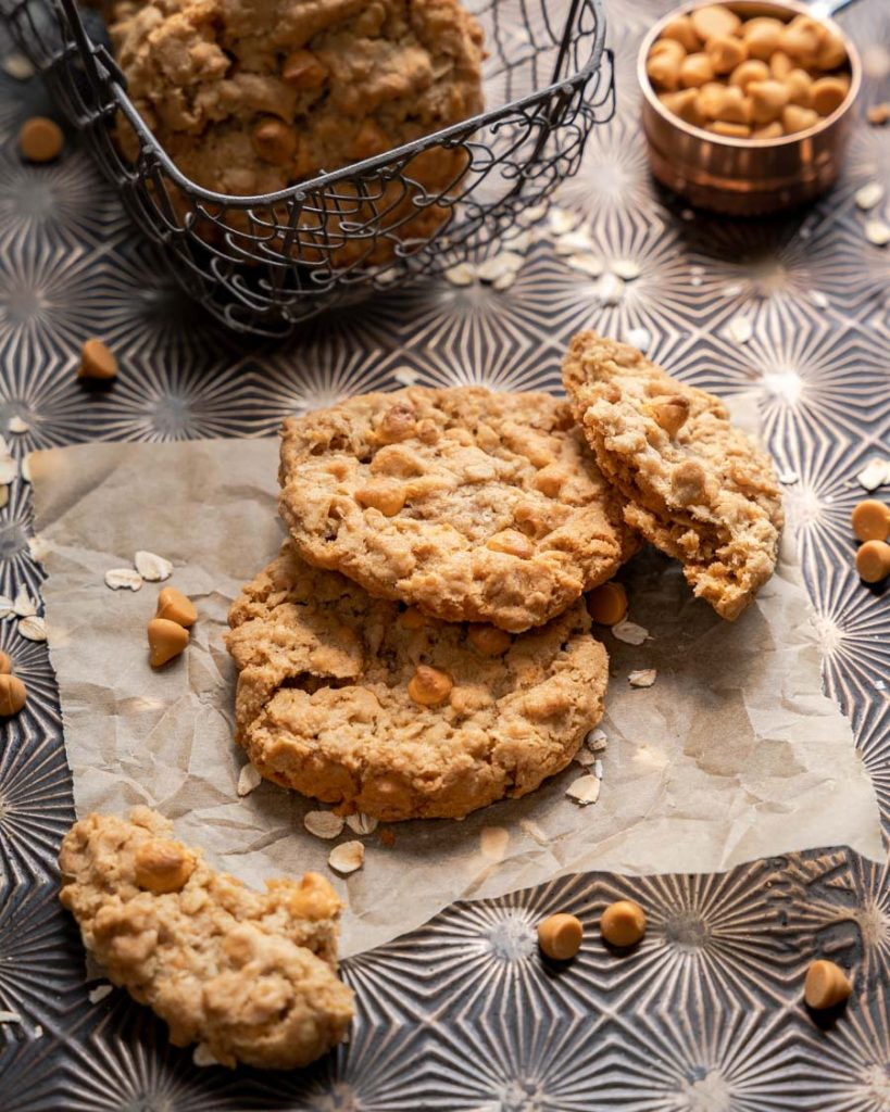 Top down view of two oatmeal butterscotch cookies with a broken cookie leaning against them.