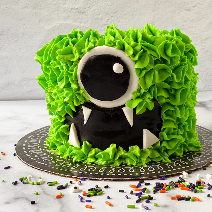 A cake decorated to look like a green monster with black eyes and fangs sprinkles scattered around it.