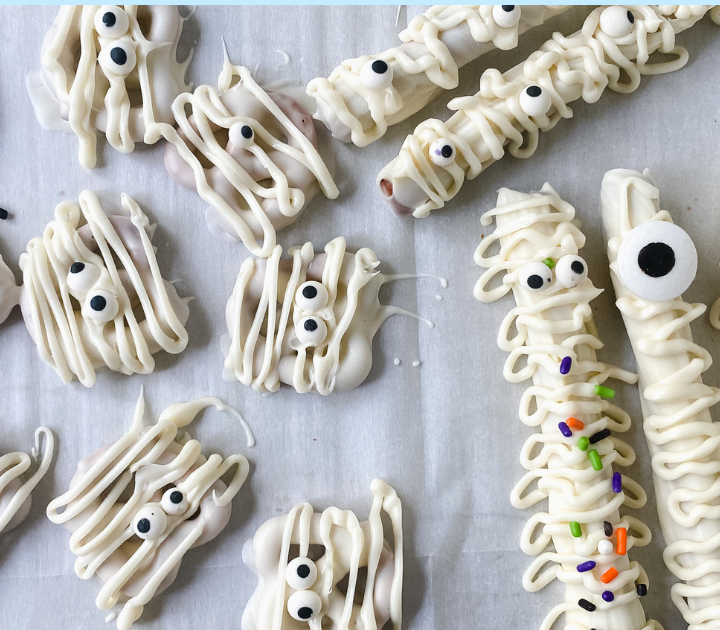 Pretzels drizzled with white chocolate and garnished with candy sprinkles and eyeballs to resemble mummies.