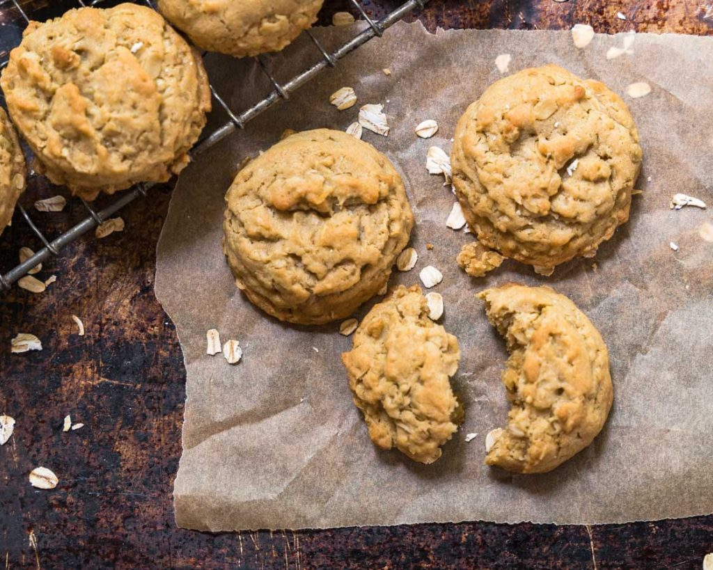 Three oatmeal cookies on a piece of parchment paper.