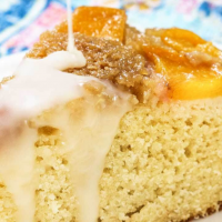 A slice of peach cake with glaze drizzled over the toop.