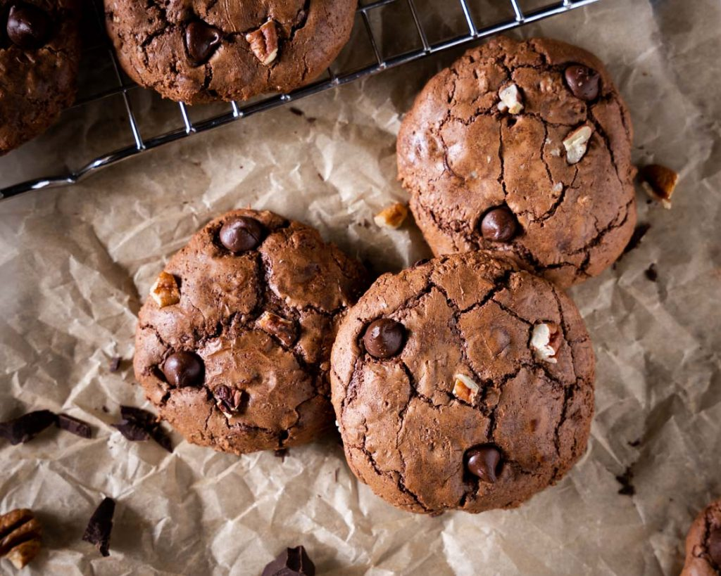 Top down view of three chocolate cookies filled with chocolate chips and nuts.