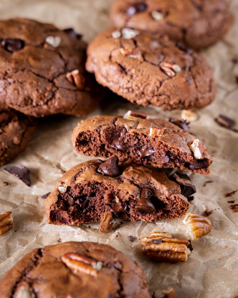 Front view of a chocolate brownie cookie cut in half showing chocolate chips and chopped nuts.