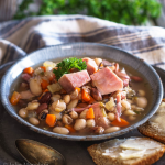 A bowl filled with ham, beans, carrots and celery.